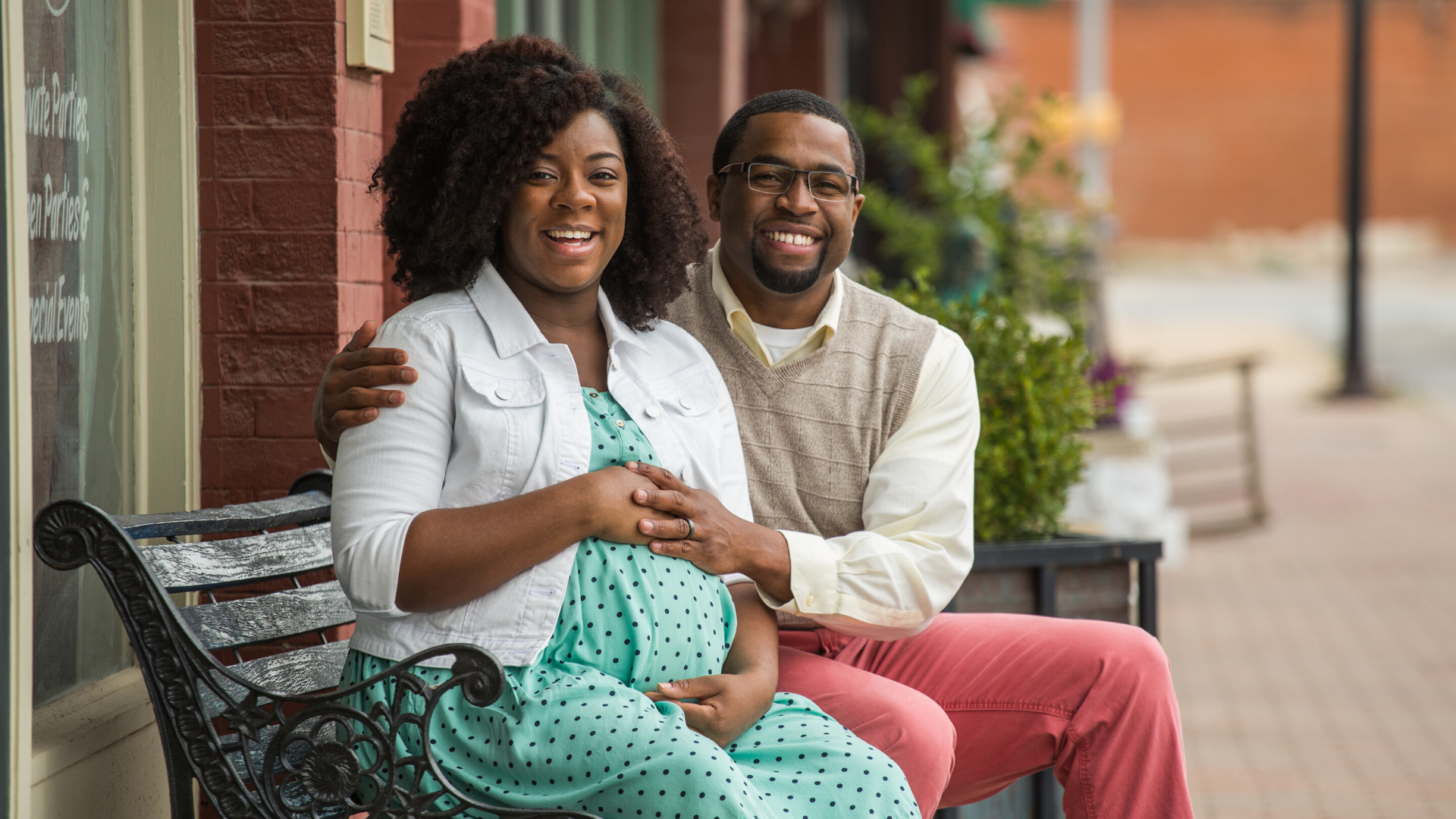 African American pregnant Couple sitting on a bench